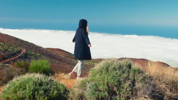 Nő sikeres túrázás hegymászás, motiváció és inspiráció a felhők felett. A hegytetőn kinyújtott hegymászó karok inspiráló tájat látnak.