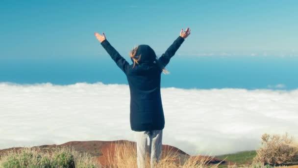 Szabadság utazó nő áll emelt karokkal a hegy tetején Tenerife és élvezze a gyönyörű felhők felett, utazás, szabadság, Kanári-szigetek