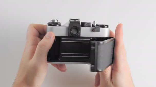 An unrecognized man opens the body of an old retro vintage photo camera to replace the film.