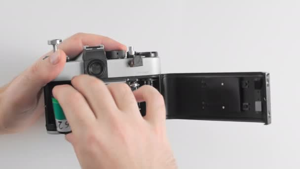 An unrecognized man inserts green film into the body of an old vintage retro camera