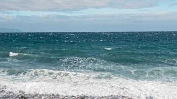 Tengeri szörf. Óceáni part, türkizkék víz és fehér hab hullámai. Csepp repül a kamerába, vulkanikus fekete part kövek és homok
