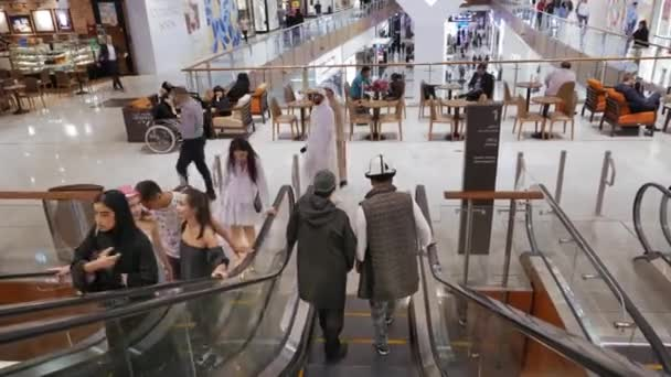UAE, Dubai - February, 2020: Two men in Kazakh folk clothes in the worlds largest shopping mall Dubai Mall in the Arab Emirates. A man in a wheelchair rests in the background.