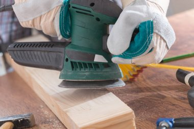 Man sanding a wood with orbital sander
