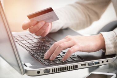 Womans hand holding credit card over laptop