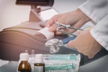 pharmacist or medical doctor using cash register