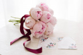 Svatební pozvánky s volným místem pro text vedle krásné kytice růžových pivoňky