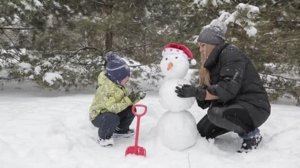 Mutter und Sohn machen einen Schneemann 11