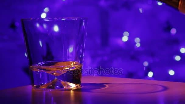 Whisky nalil do sklenice / whisky nalil do sklenice na pozadí vánočních světel