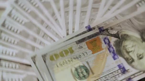 A százdolláros bankjegyek egymás hegyén-hátán fekszenek és forognak, közelről.