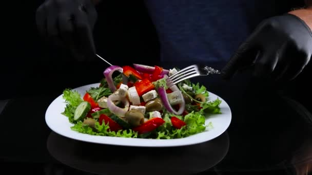 A black-gloved cook is stirring a Greek salad with a fork and knife. The footage was shot in slow motion