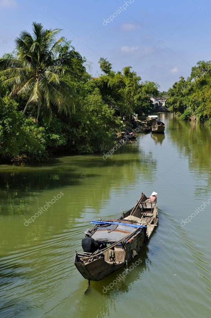 Small wooden motorboat passing through a water channel surrounded by tropical vegetation, Hue, Vietnam, Asia