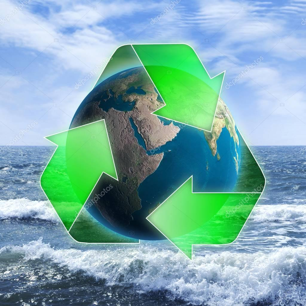 Recycling symbol with a globe over a seascape, environment and ecology concept