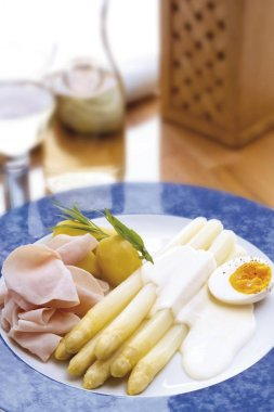 White asparagus, hollandaise sauce, boiled egg, slices of cooked ham and potatoes
