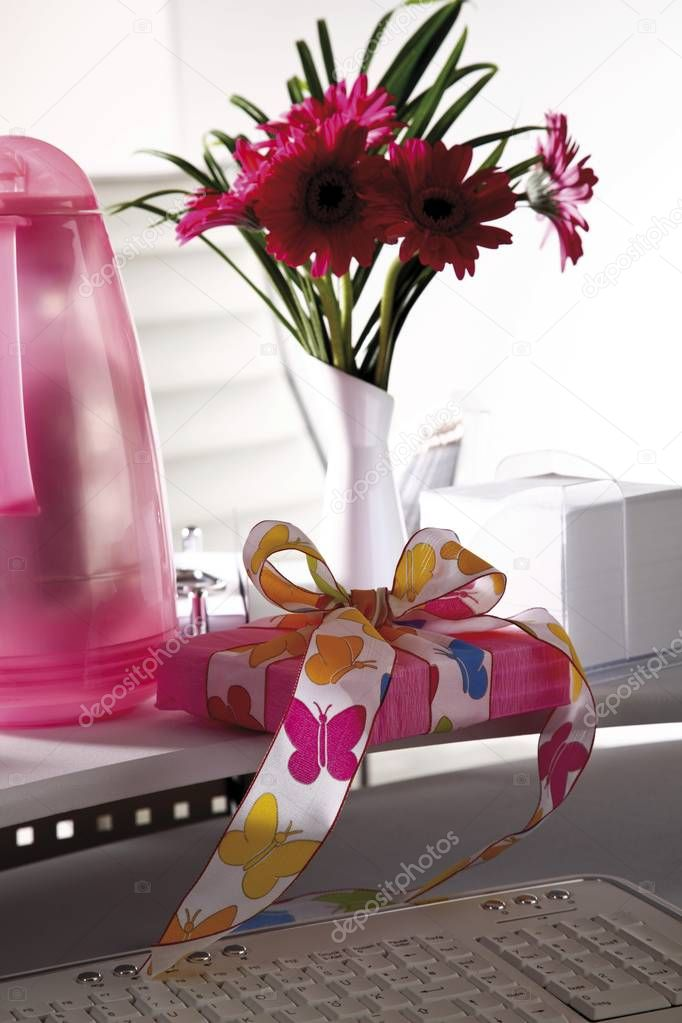 Desk, small flower bouquet and a parcel