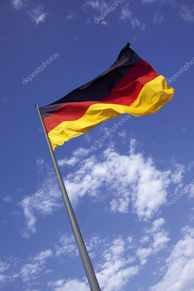 German flag on flagpole flapping in the wind in front of a blue sky