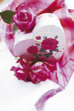 Heart-shaped gift box with roses on a silky cloth