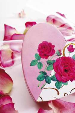 Heart-shaped gift box with rose petals and champagne glasses