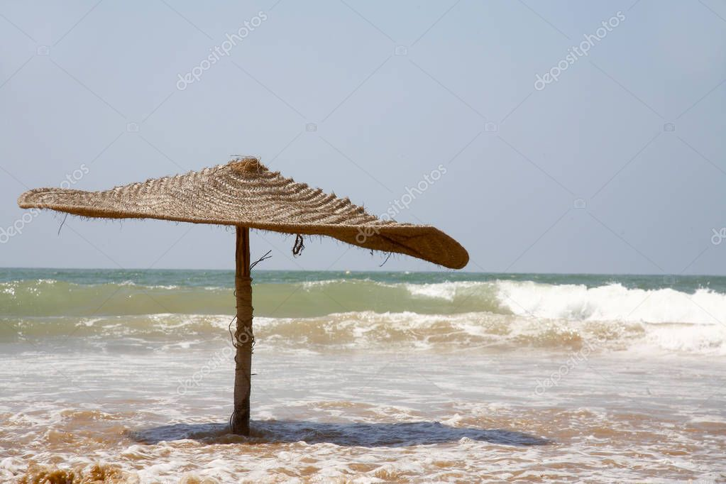 Parasol in the water, surf on the beach