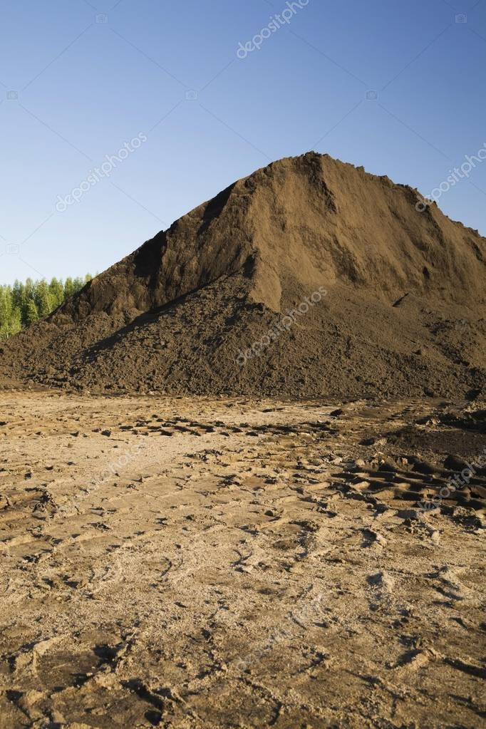Heavy tire tracks and a mound of topsoil in a commercial sandpit, Quebec, Canada, North America