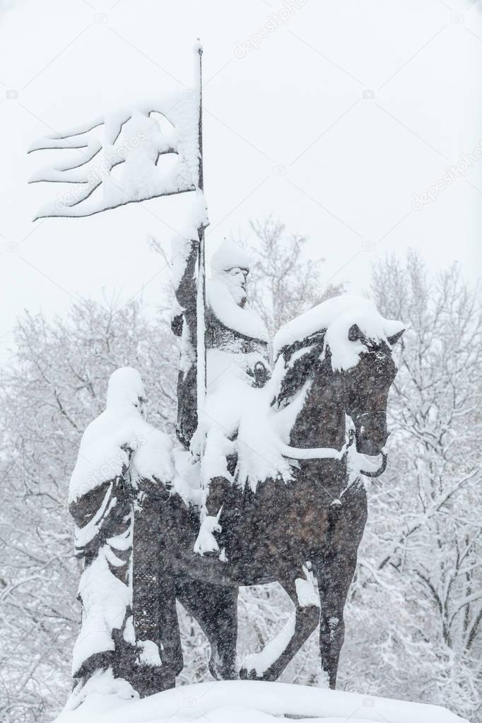 City after blizzard: the monument of prince Vladimir covered with snow.