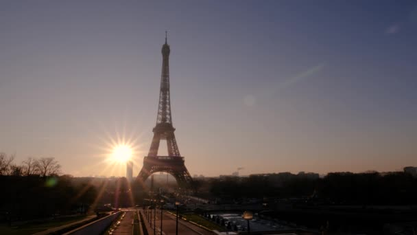 View of the Eiffel Tower from the Trocadero Gardens at dawn. The sun rises from the horizon.