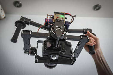 Camera carbon gimbal with dslr camera with man hands
