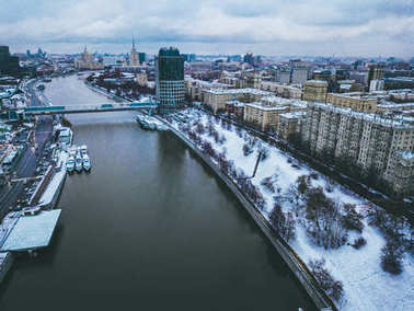aerial view of city architecture near river during snowy winter