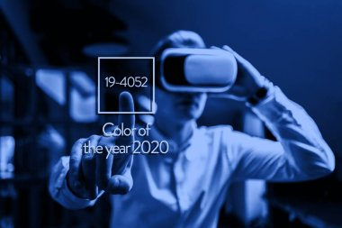 amazed office worker use electronic vr glasses, color of the 2020 year trend, classic blue tone