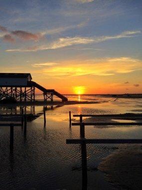 Sunset at wadden sea with stilt houses