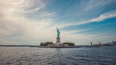 view of Statue of Liberty on New York City skyline at sunny day