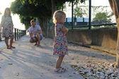 Fotografie Das Mädchen nahm Anstoß an ihren Eltern, faltete ihre Hände auf ihren Bauch und schmollte. Die Eltern schauen sie an. weiche Sonnenstrahlen. Morgengrauen. Sonnenuntergang