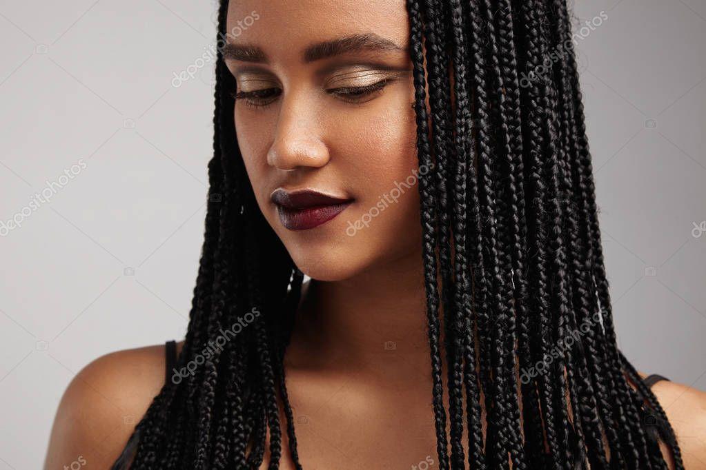 Closeup portrait de femme noire avec tresses sur fond gris \u2014 Image de