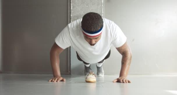 Young man makes push-ups and bites a doughnut cake