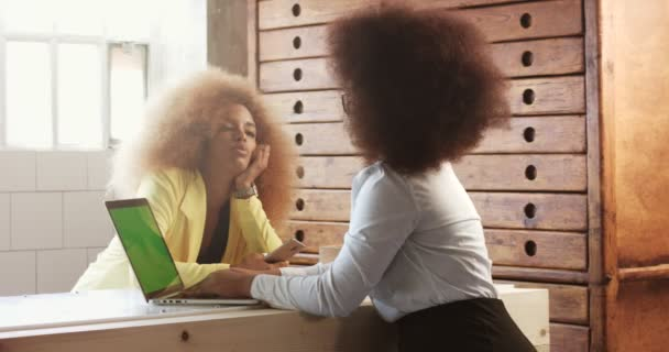 two black woman with afro hair in office has a small talk during a work process