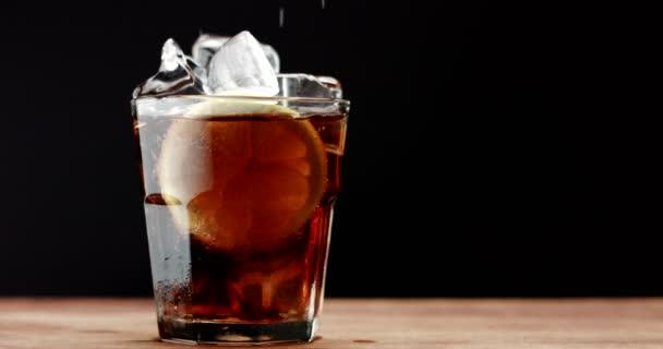 Glas mit Eiswürfeln und Zitronenrutsche und Cola. von Cola, frischem Getränk, Eiswürfeln und Blasen