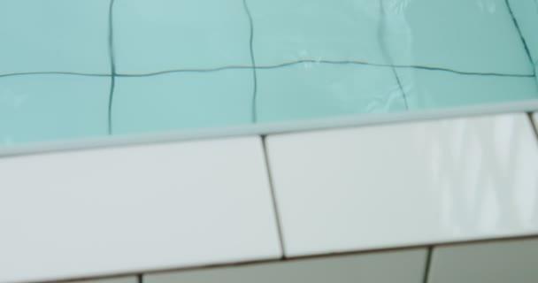 nakloněná rovina hnutí na ženu sedící v bazénu a bavit se s vodou
