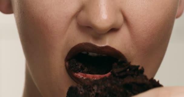 Nahaufnahme von Frau s Wouth machen mit einer Schokolade Lippenstift Farbe steigerte Essen ein Stück Schokolade cke