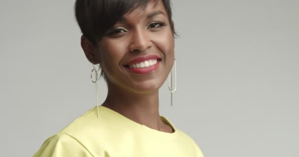 Beautiful African woman with large earrings in yellow top