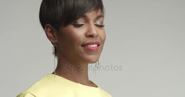 schöne afrikanische Frau mit großen Ohrringen in gelbem Top