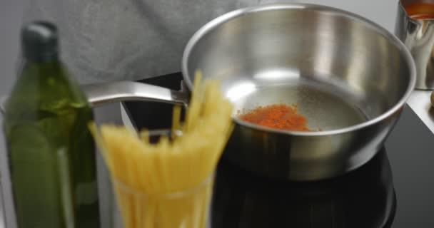 Přidání papriky na rozpáleném oleji v pánvi