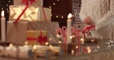 Cute young woman in cable sweater wrapping presents