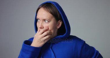 Woman in blue hoodie showing changing emotions