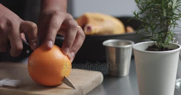 Mužské kuchaři připravují pečené kuře s pomerančem a rozmarýnem