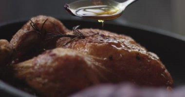 Basting roasting chicken with oil and juices
