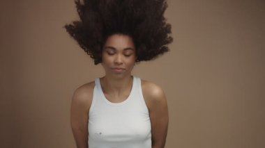 slow motion of black woman lifting head and shaking hair