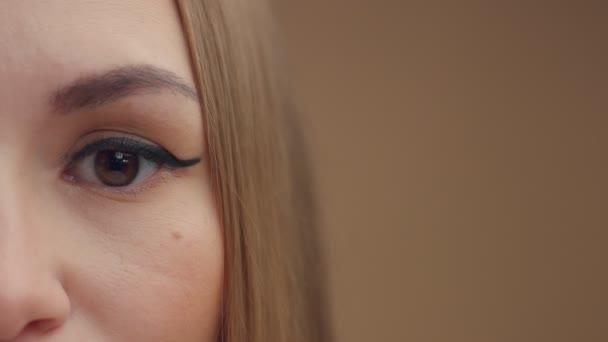 Zenske oko při pohledu na fotoaparát. Polovina tváře closeup