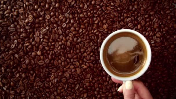 pohled shora ruky šálek černé kávy ji na pozadí fazole káva