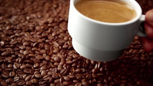 vista laterale della tazza di caffè nero bianca sui chicchi di caffè