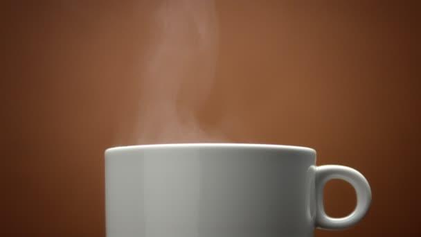 Closeup bílý hrnek s horkým nápojem. Pára z poháru