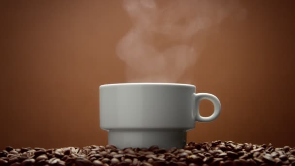 white cup on coffee beans with steam from hot drink